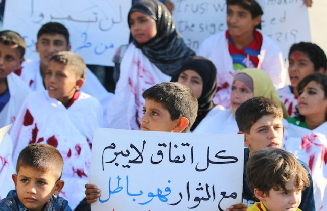 A boy carries a placard during a demonstration against forces loyal to Syria's president Bashar al-Assad and calling for aid to reach Aleppo near Castello road in Aleppo